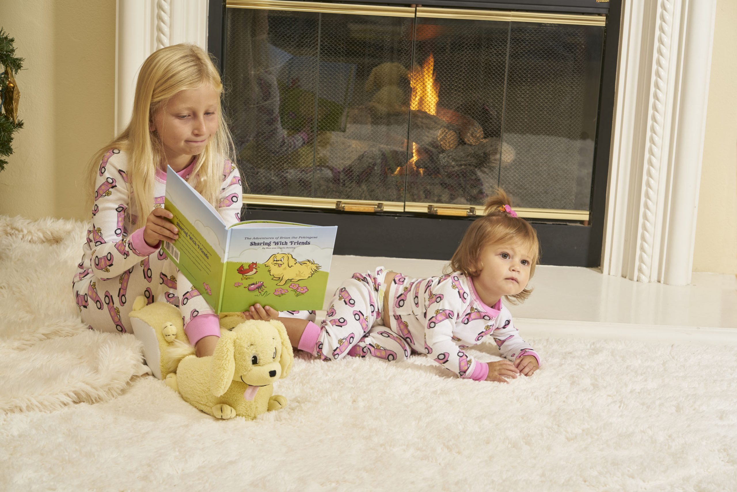 girl wearing pajamas with book and toddler