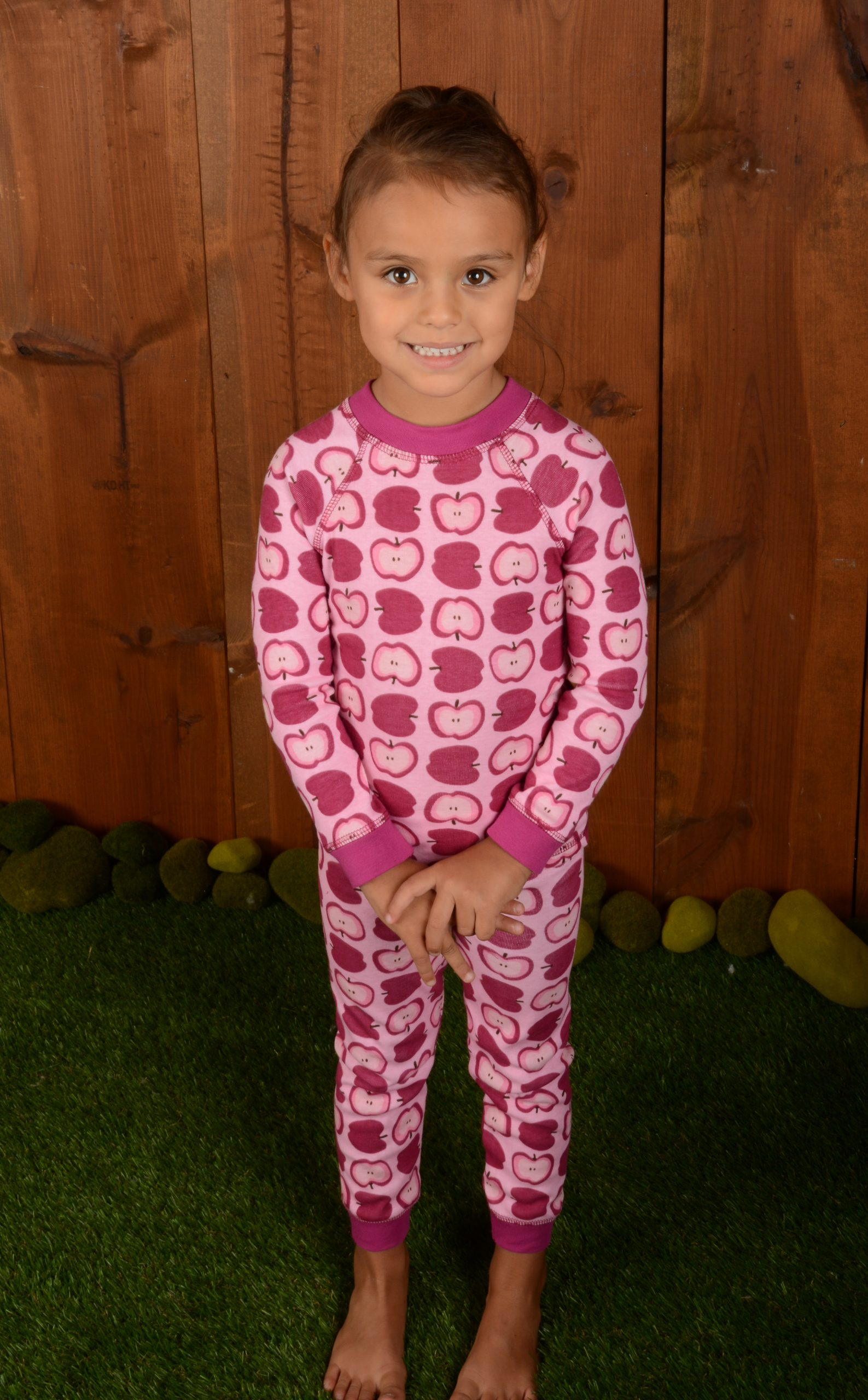girl wearing apple print pajamas