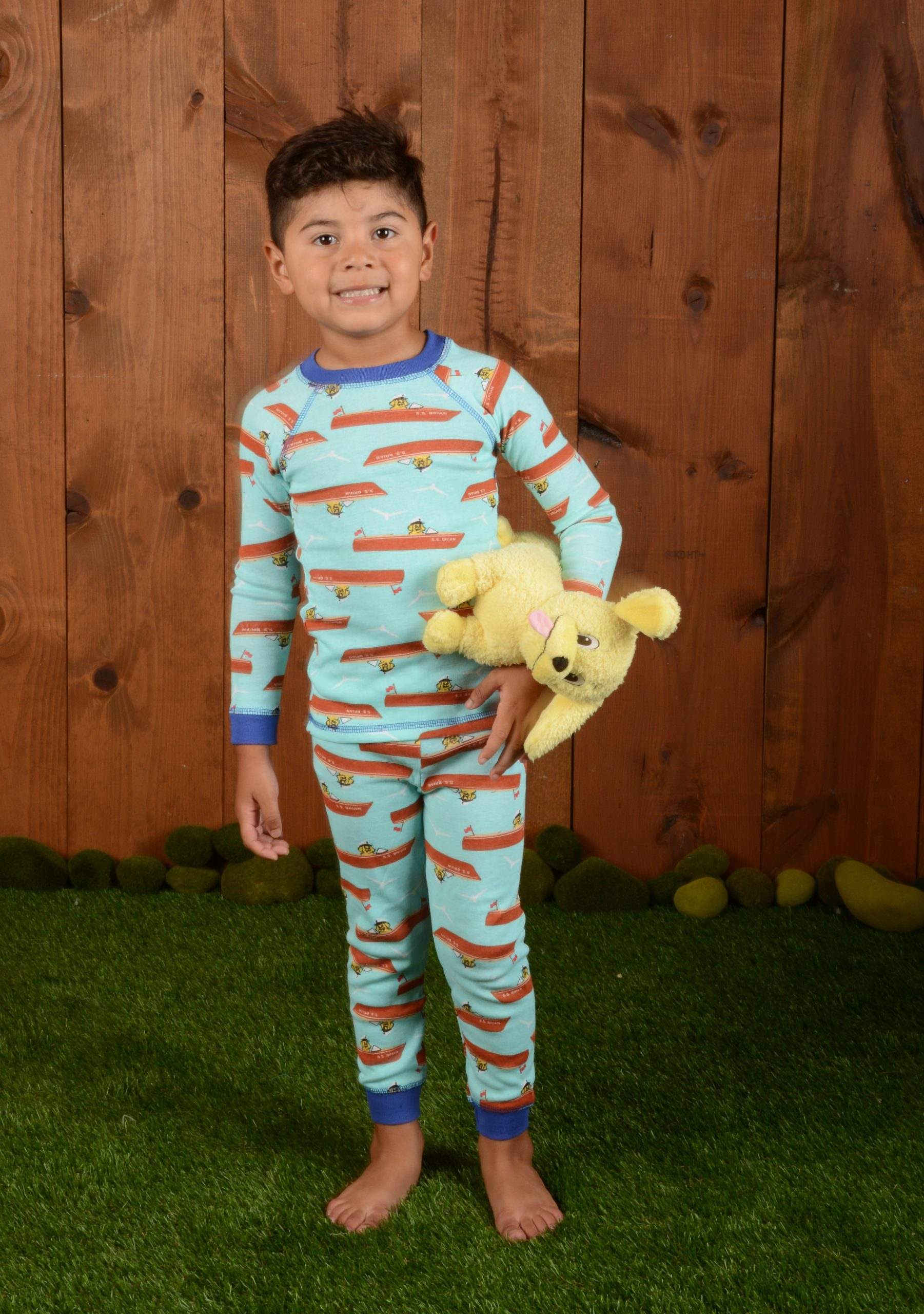 boy with boat print pajamas and plush toy