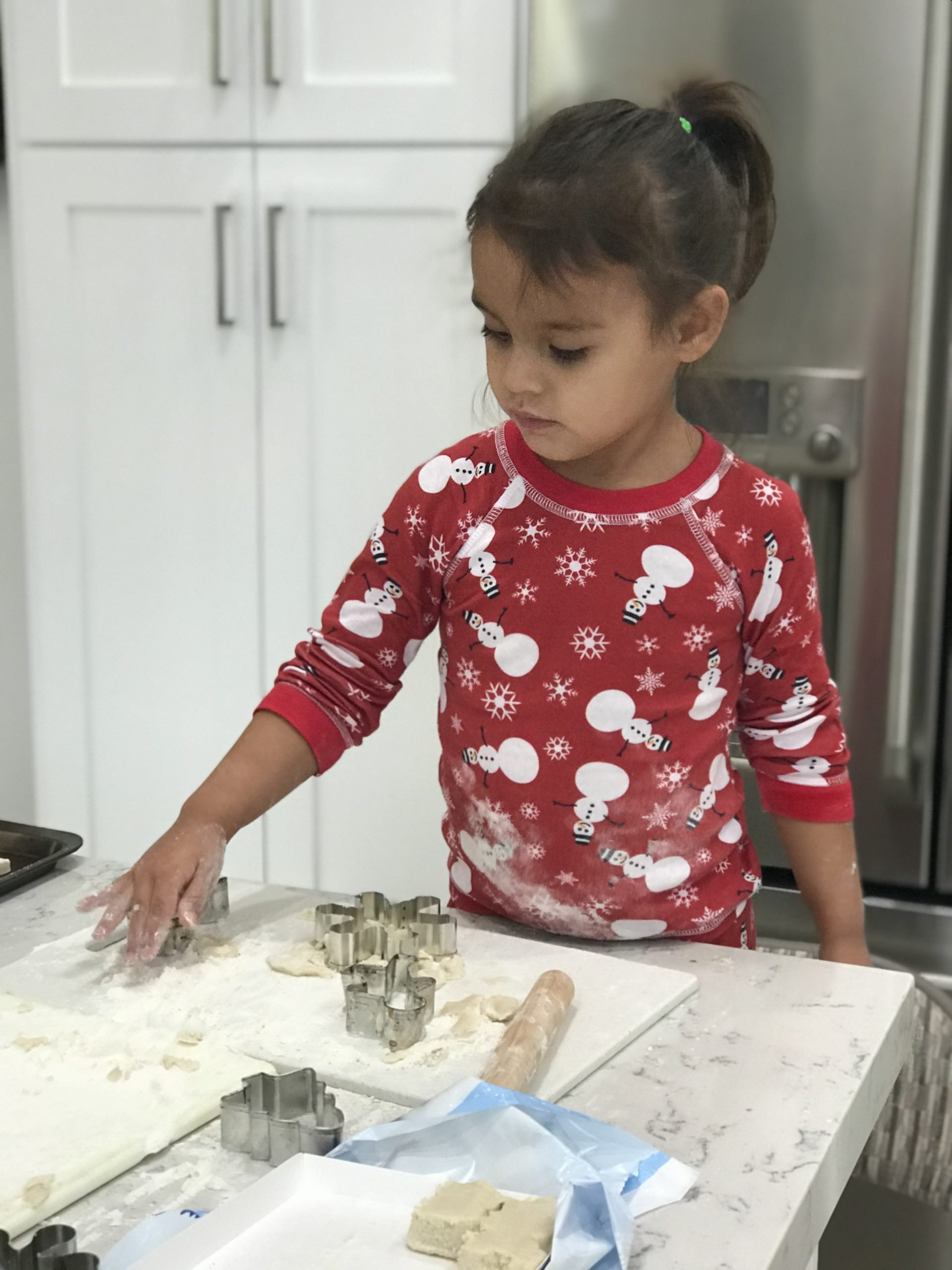 girl wearing snowman print pajamas making cookies