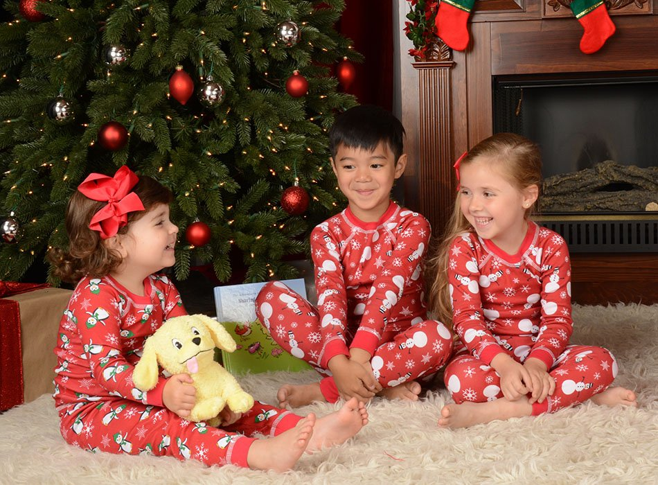 children wearing holiday pajamas in front of fireplace