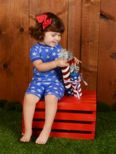 girl wearing pajamas with blue star fourth of July print
